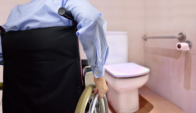 Handicap man in a wheelchair in front of a toilet